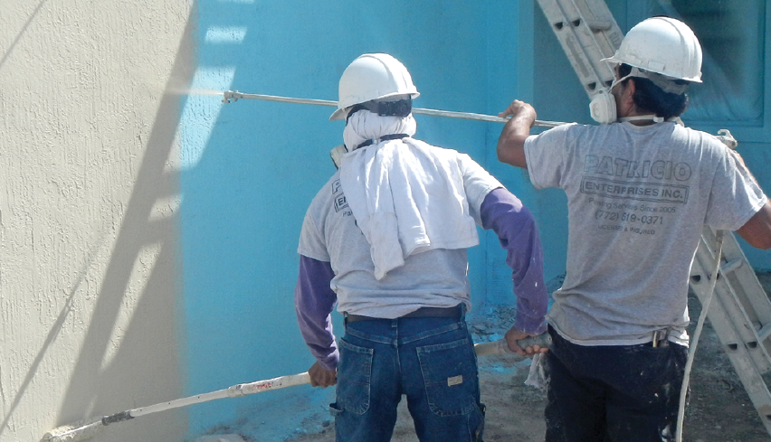 Two construction crew members painting a stucco wall on the jobsite