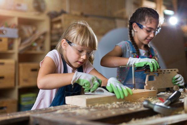 Two girls in a wood workshop planing and sanding their woodworking projects
