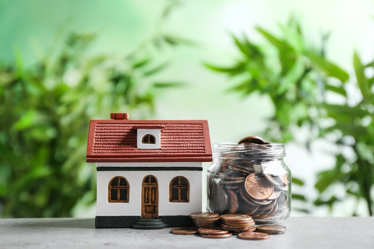 Concept photo of home figurine with coins