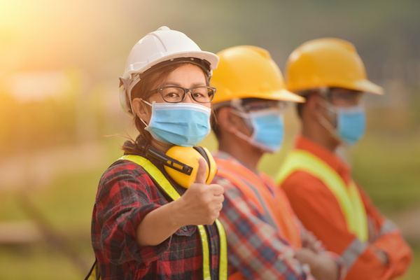Construction employees wearing masks, one gives a thumbs up