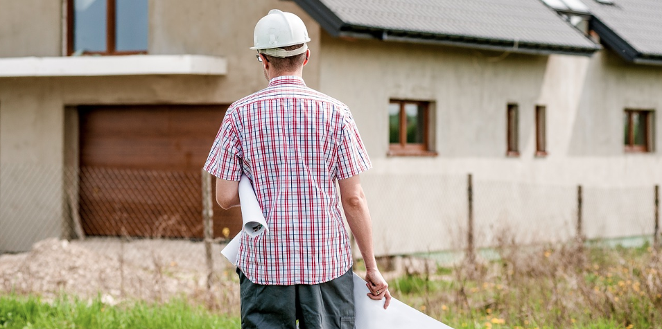 Home builder walking toward house with plans in hand