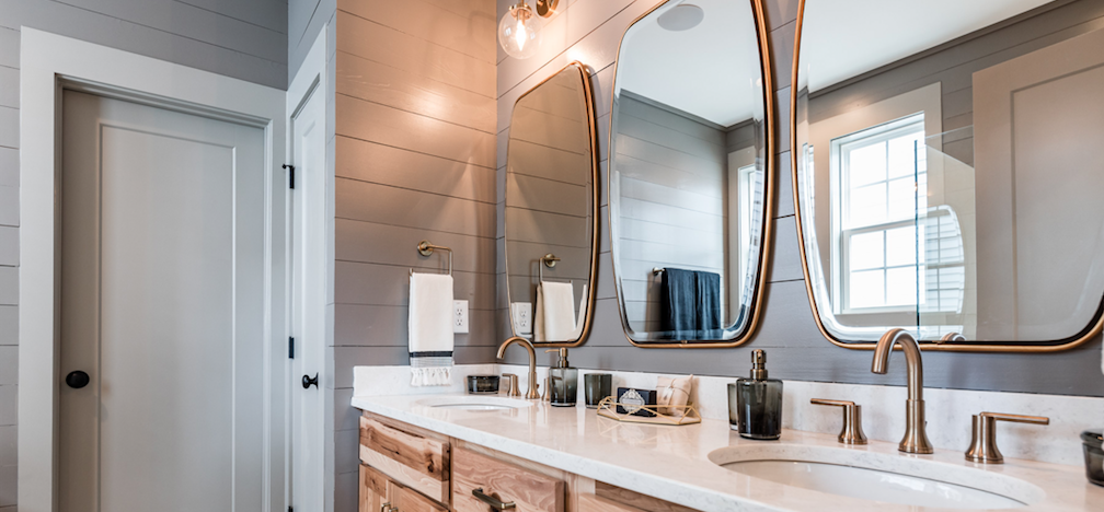 this master bath design from Garman Homes has accent tile and brass fixtures—two features homebuyers want today