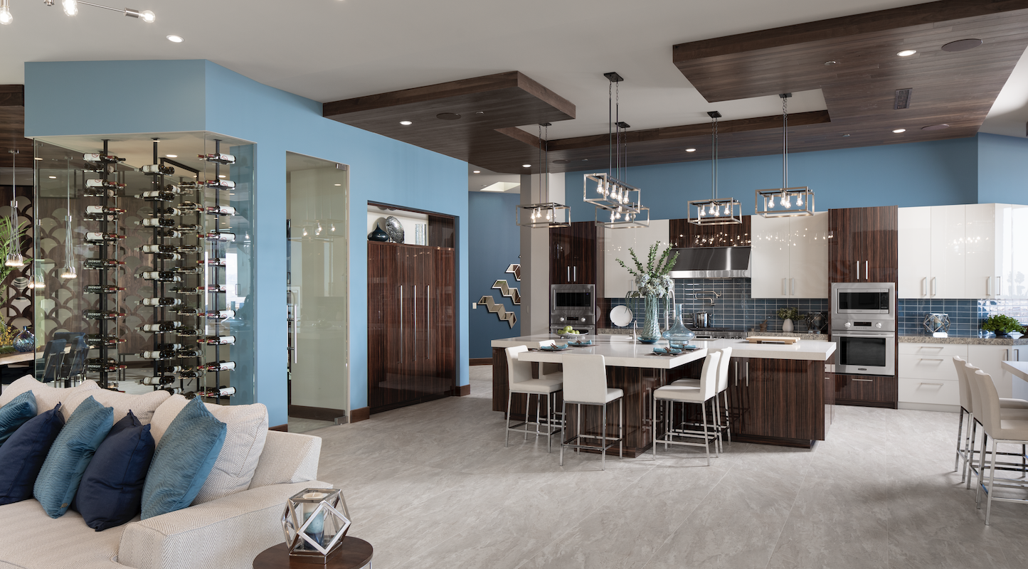 The New American Home kitchen with island and wine storage opening onto the living-room