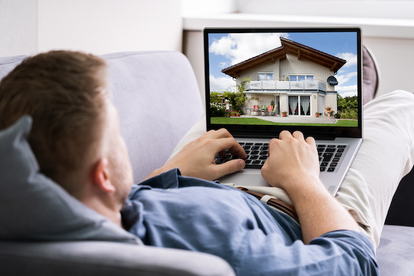 man looking at home on laptop for buying home online