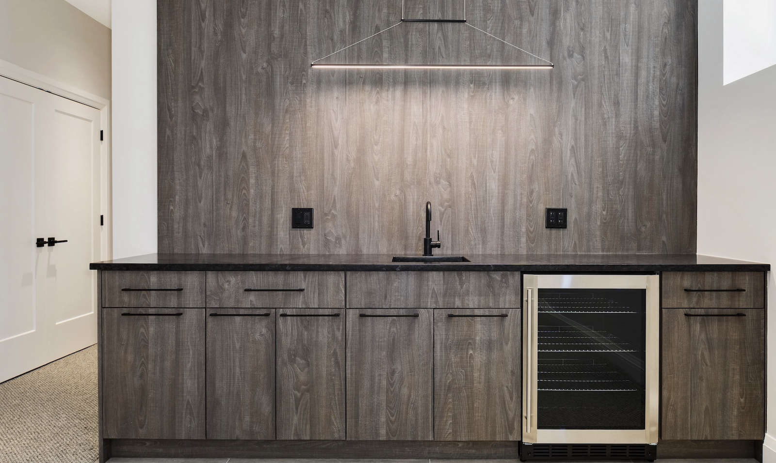 The faux range hood above the countertop is created by LED lighting