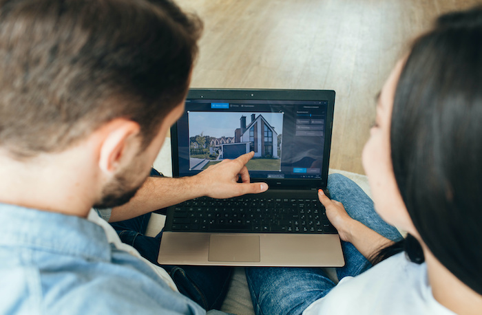 Couple looking at buying a home virtually on laptop