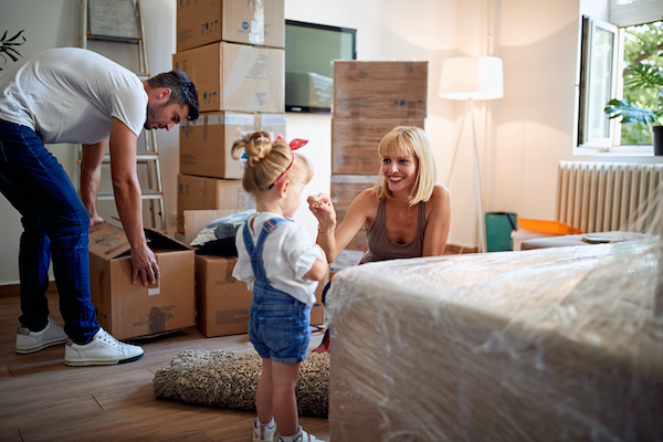 young family packing boxes in bedroom in preparation for moving house