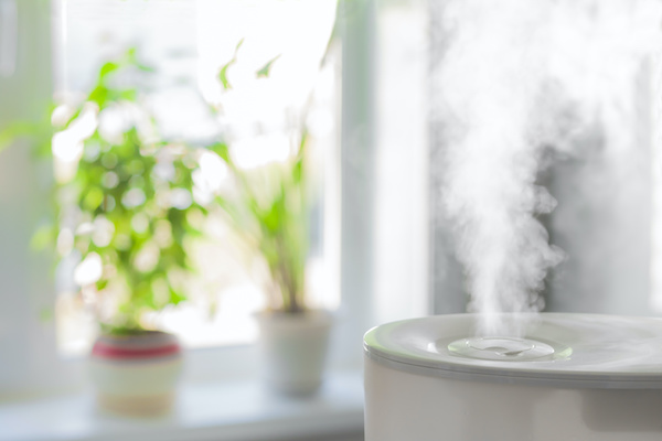 A humidifier in a home with indoor plants on the window sill for healthier indoor air