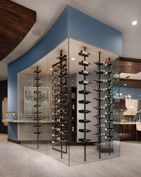 The New American Home dramatic glass display for wine storage adjoining the kitchen