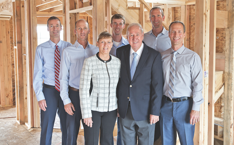 Olthof Homes' management team standing in one of the company's homes at the framing stage