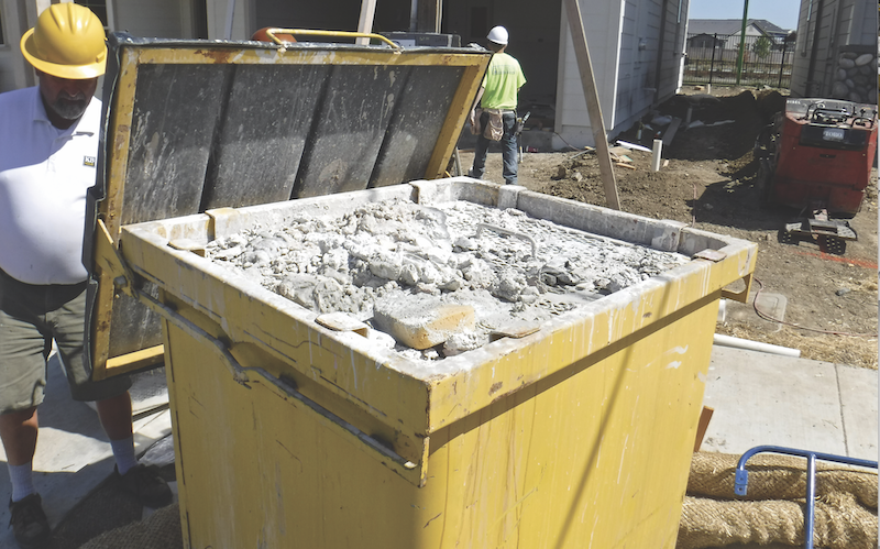 steel bin on construction site for collecting paint and plaster slurry