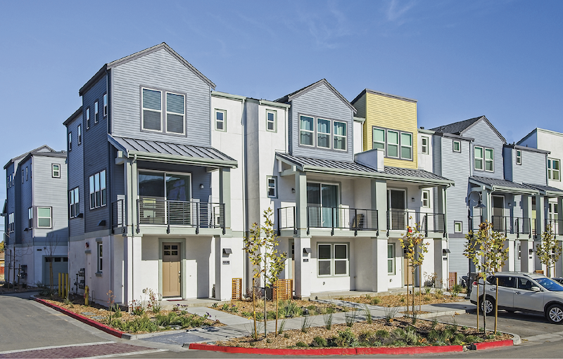 front facade of infill housing development Nova at the Vale, yellow-blue-gray color scheme