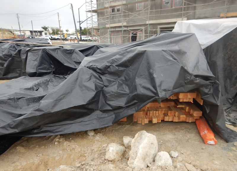 lumber on jobsite covered by plastic tarp for protection from weather