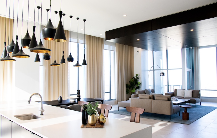 Black pendant task lighting adds a sculptural feel to the open-plan kitchen/living space
