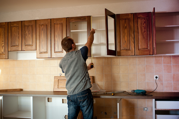 contractor installing new kitchen cabinets in home