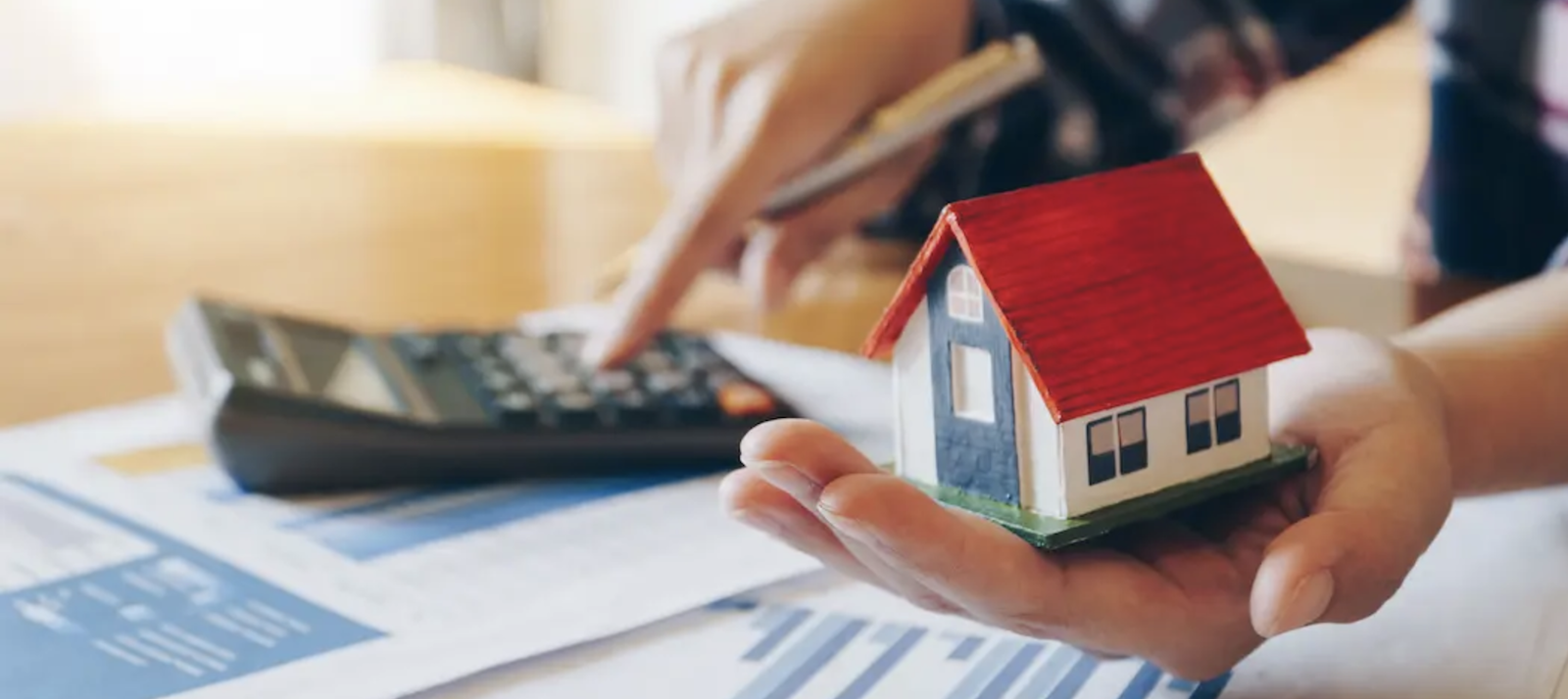 Man holding home figurine in one hand while using calculator to calculate home mortgage with the other hand