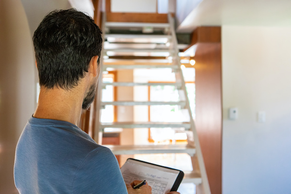 home inspector assessing staircase and other features in home