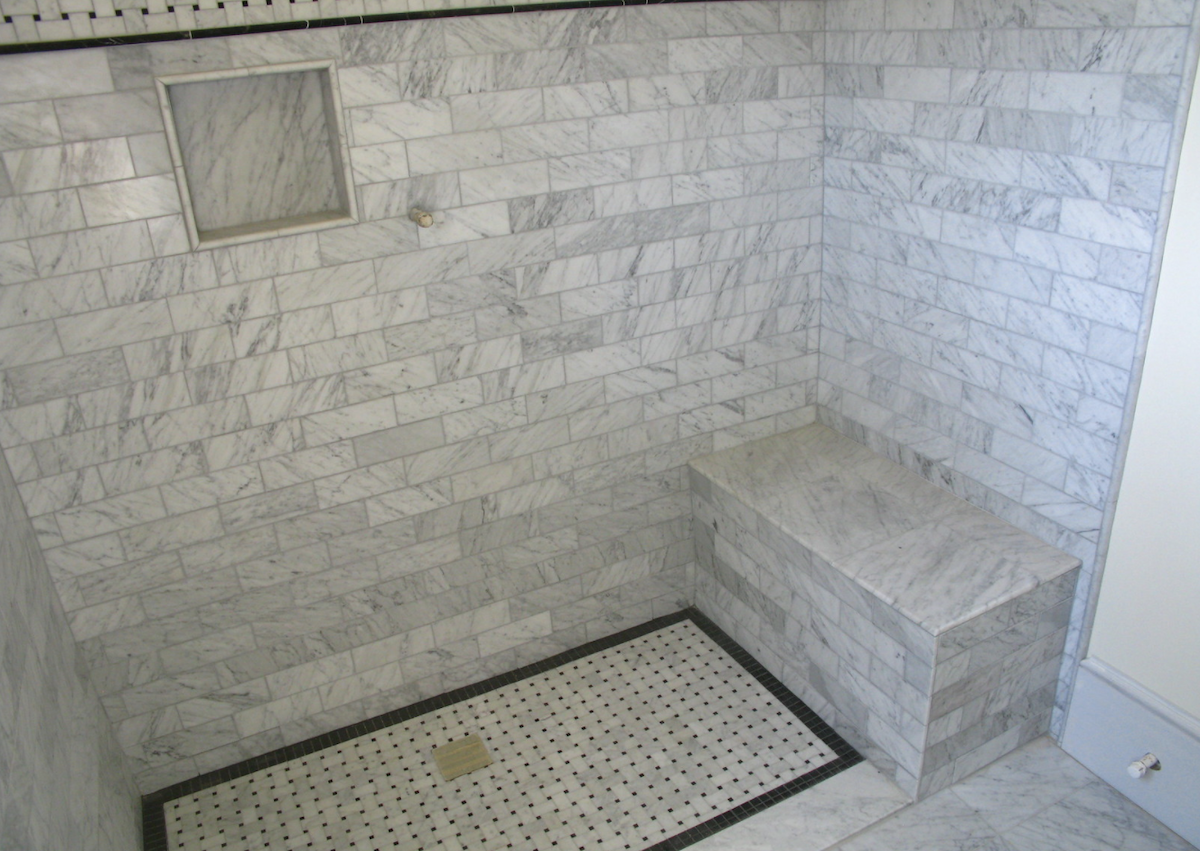 Marble tile shower stall with shower bench and storage nook
