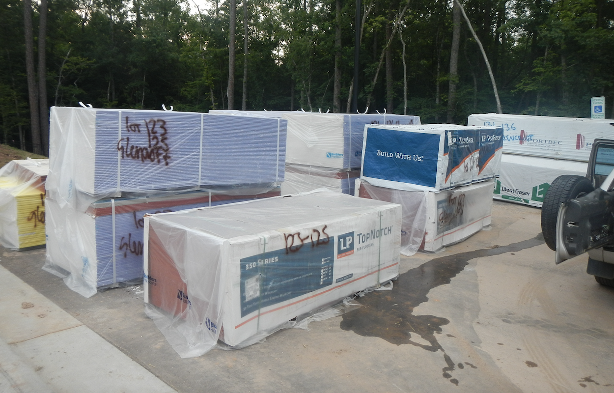 materials stored on construction site covered with plastic to prevent them getting wet