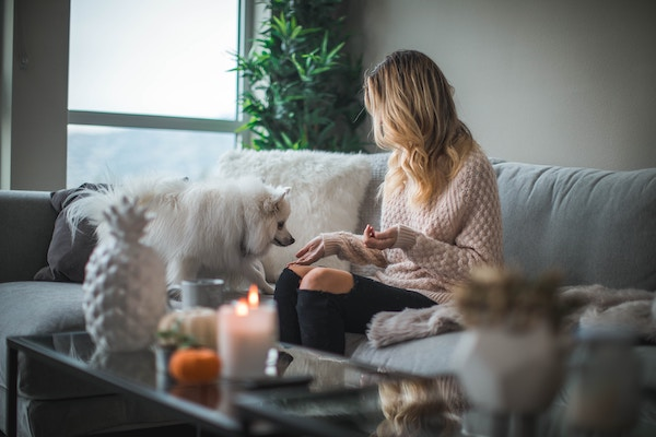 Millennial woman at home sitting on the couch with her dog
