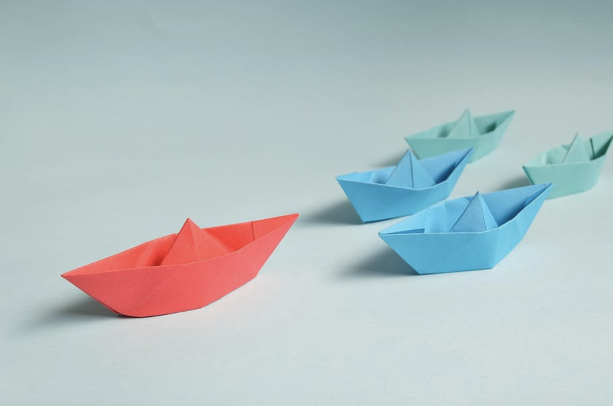 one red paper origami boat leading ahead of smaller blue origami boats