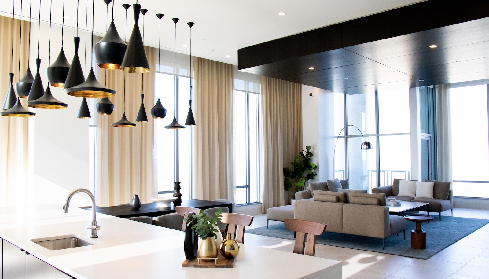 Sculptural black pendant lighting hangs over kitchen island