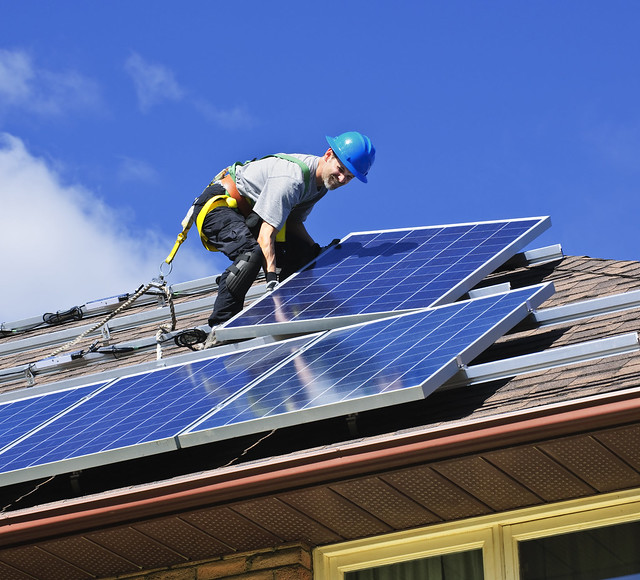 Solar-energy-mandates-worker-installing-rooftop-solar-panels