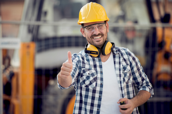 smiling builder on jobsite wearing hardhat