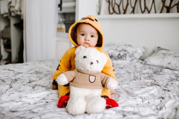 Child seated on bed with teddy bear