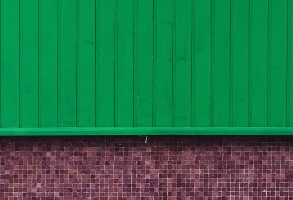 Green siding over brick wall
