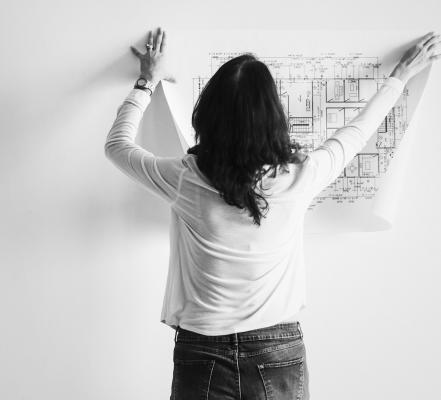 Woman hanging up floorplans on wall