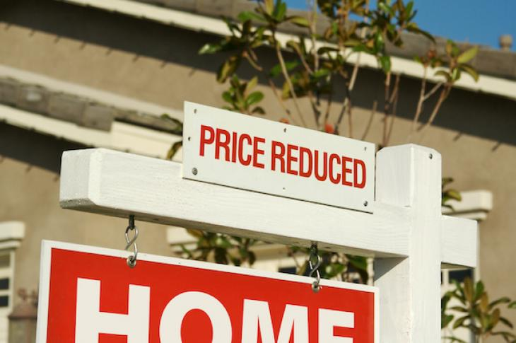Home for sale sign with 'price reduced' sign at top