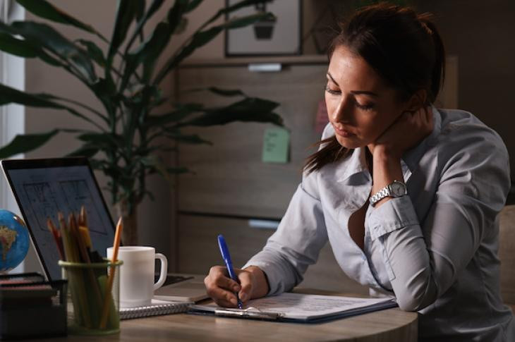 Woman sitting at desk filling out paperwork