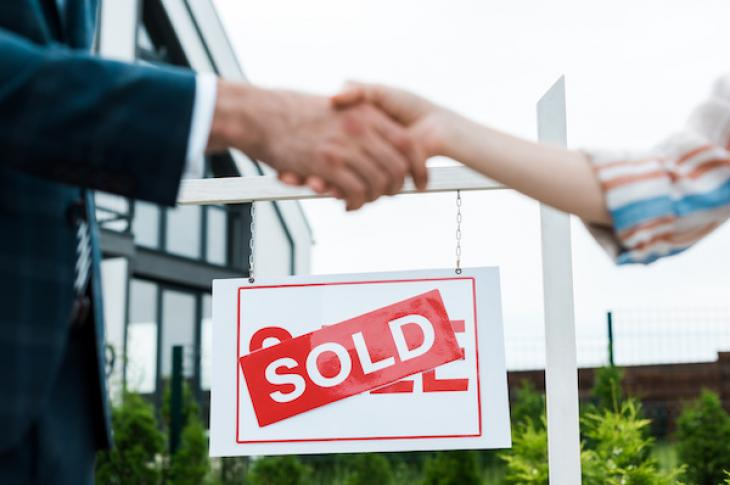 Broker and buyer shaking hands with a home sold sign behind them