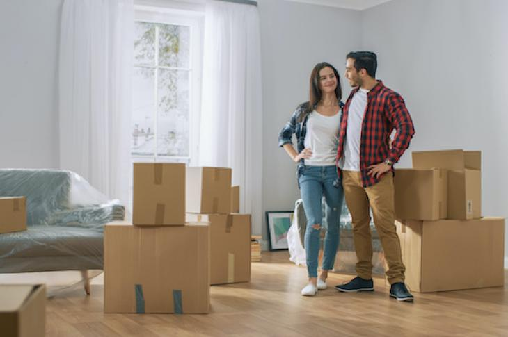 Smiling couple in room with moving boxes