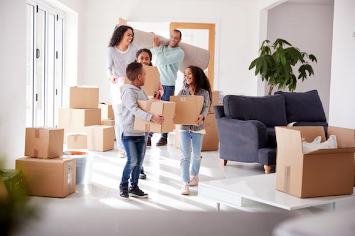 Family smiling while holding moving boxes