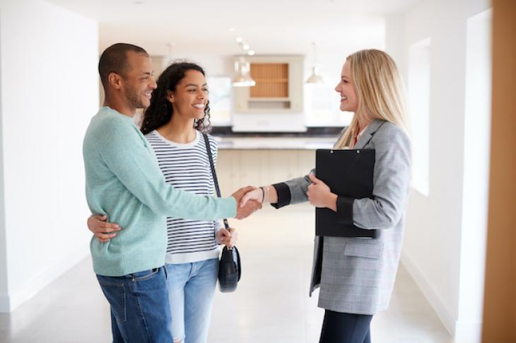 Smiling couple shakes hands with realtor inside a home