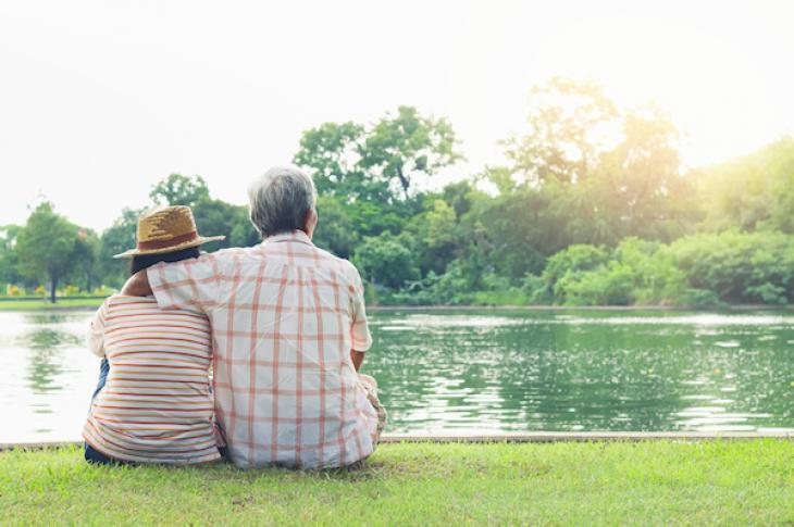 An older couple sitting by a lake
