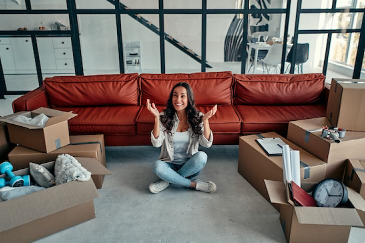 Woman sitting on floor of new house smiling with boxes around