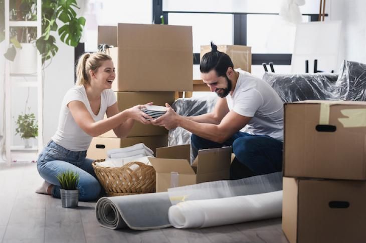 Couple laughing as they pack moving boxes