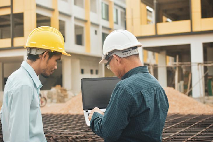 Two construction workers using a laptop