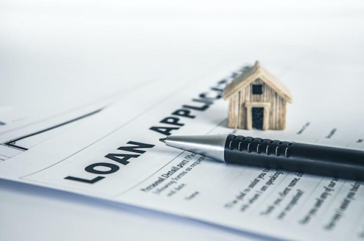 Loan application with home figurine and pen