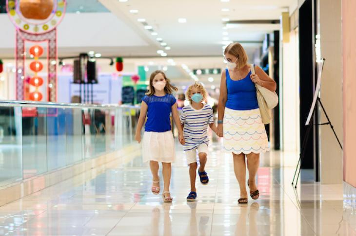 Mother and children wearing masks while walking through mall