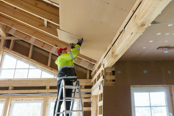 Home builder adding insulation to ceiling of home