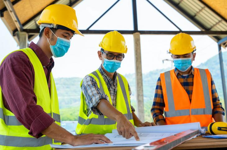 Three builders review blueprints while wearing face masks