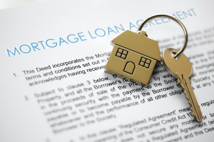 Mortgage application in background with home keys on top