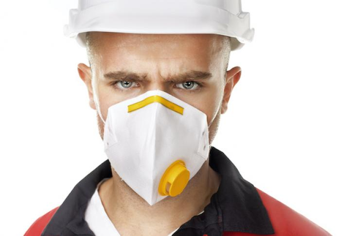construction worker wearing face mask to protect against both dust and the coronavirus