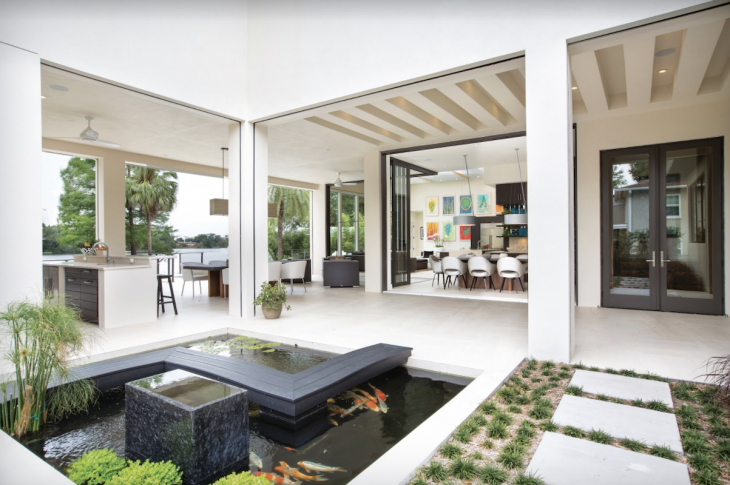 modern home outdoor living space with large openings, summer kitchen, and koi pond