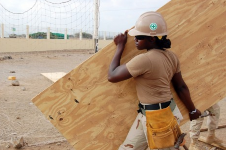 Woman with hard hat carrying plywood