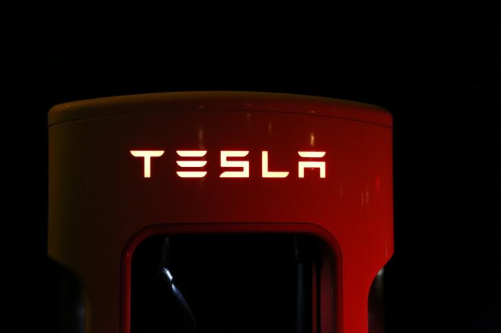 TESLA logo, red with yellow lettering on black background